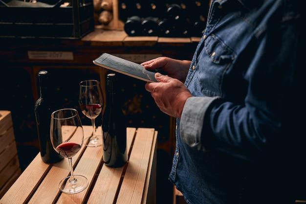 Mężczyzna w dżinsowej koszuli stojący z tabletem w piwnicy winiarni. szklanki i butelki czerwonego wina na drewnianej skrzyni