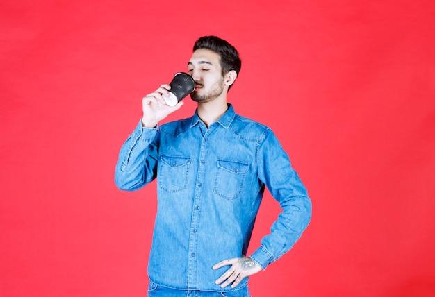 Mężczyzna w dżinsowej koszuli trzyma czarną filiżankę jednorazowego napoju i pije go.