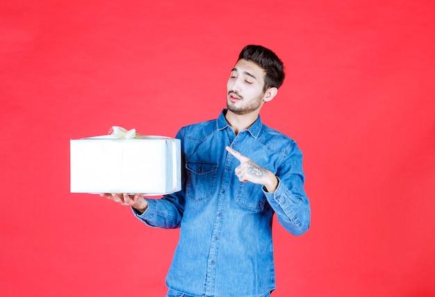 Mężczyzna w dżinsowej koszuli trzyma srebrne pudełko i wskazuje gdzieś.