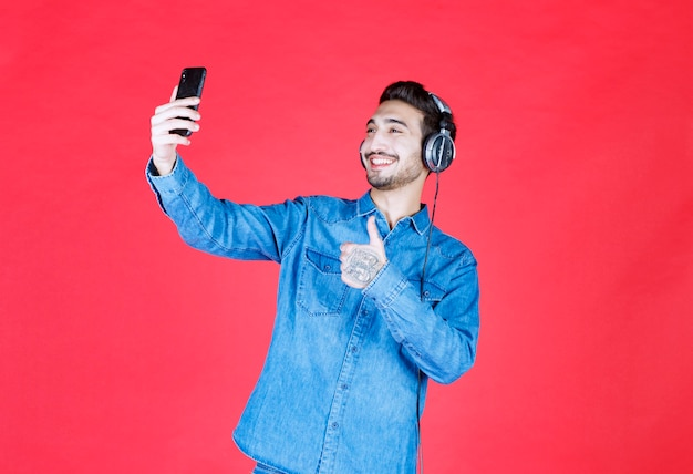 Mężczyzna w dżinsowej koszuli ze słuchawkami, robi selfie lub prowadzi wideorozmowę.