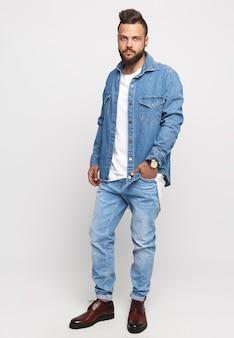 Mężczyzna w dżinsowej kurtce i dżinsach na białym tle