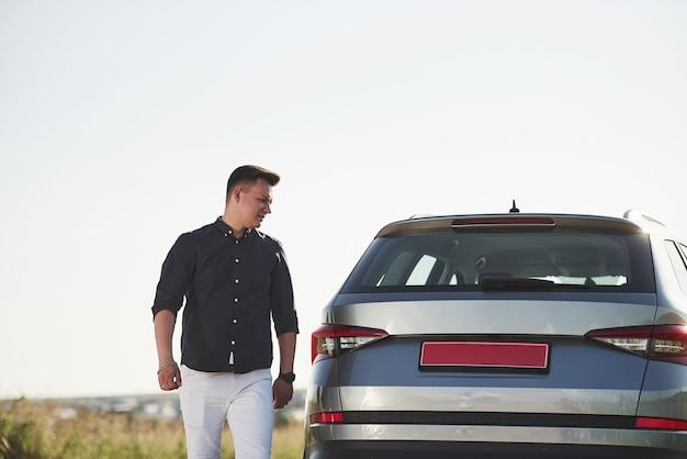 Mężczyzna w eleganckich ubraniach idzie w słoneczny dzień obok swojego srebrnego samochodu.