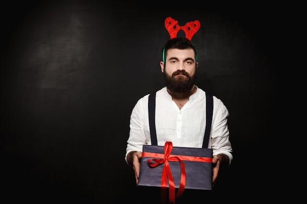 Mężczyzna w fałszywych rogach jelenia, trzymając pudełko na boże narodzenie na czarno.