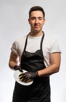 Mężczyzna w fartuchu i gumowych rękawiczkach trzyma czystego talerza