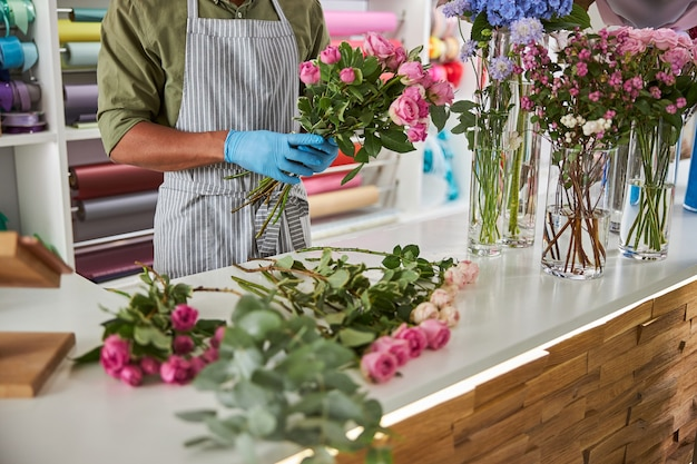 Mężczyzna w fartuchu i lateksowych rękawiczkach robi świeże bukiety różowych róż w pracy