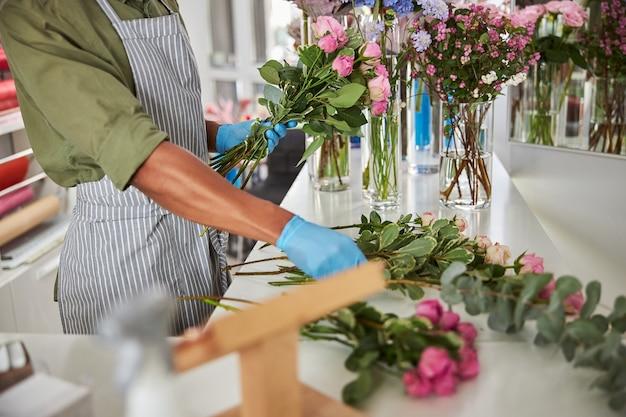 Mężczyzna w fartuchu i lateksowych rękawiczkach stoi przy ladzie w kwiaciarni i zbiera róże w pęczek