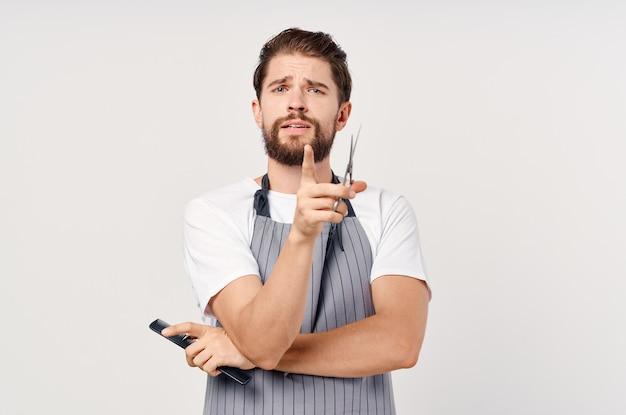 Mężczyzna w fartuchu nożyce grzebień świadczenie usług