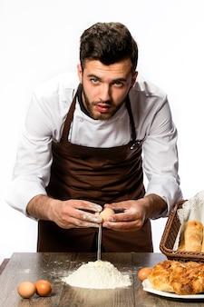 Mężczyzna w fartuchu przygotowujący ciasto,