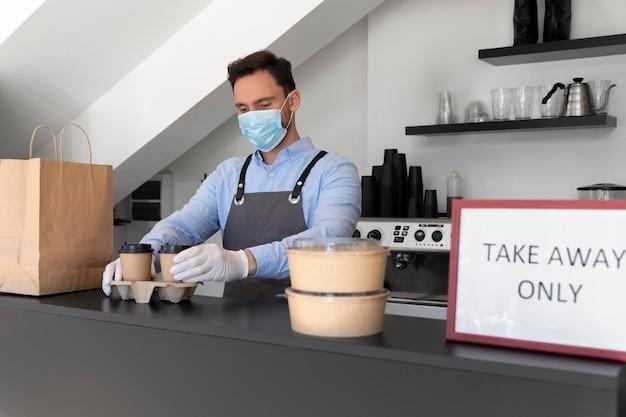 Mężczyzna w fartuchu przygotowuje jedzenie na wynos