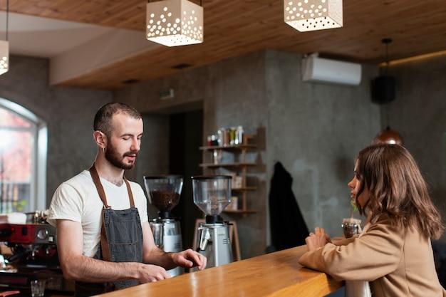 Mężczyzna w fartuchu przygotowywa kawę dla klienta