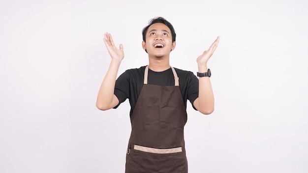 Mężczyzna w fartuchu stoi na białym tle i wskazuje w górę