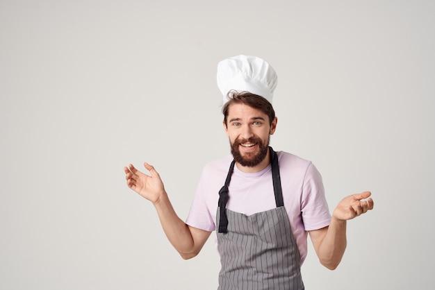 Mężczyzna w fartuchu z czapką na głowie szefowej pracy zawodowej