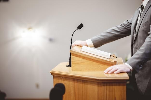 Mężczyzna w formalnym stroju, głoszący biblię z trybuny przy ołtarzu kościoła