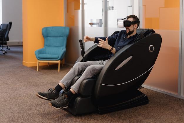Mężczyzna w fotelu masującym z wykorzystaniem technologii vr