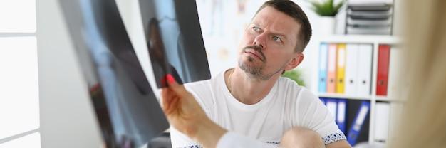 Mężczyzna w gabinecie lekarskim patrzy na zdjęcia rentgenowskie z lekarzem.