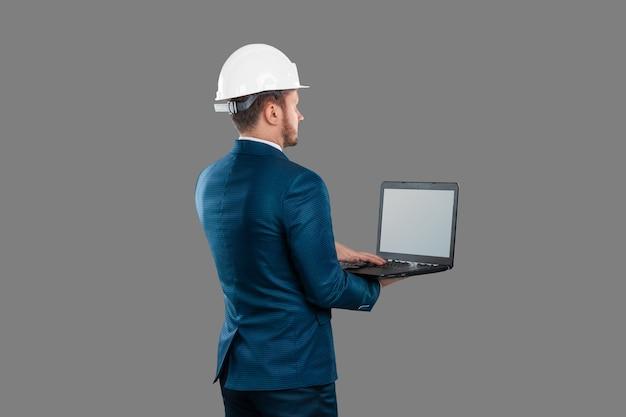 Mężczyzna w garniturze, architekt w białym hełmie na głowie