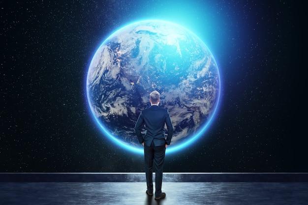 Mężczyzna w garniturze, biznesmen stoi na tle kuli ziemskiej