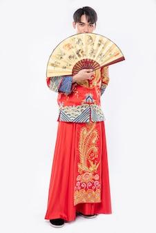Mężczyzna w garniturze cheongsam pokazuje chińskiego wachlarza na wielkim wydarzeniu w chiński nowy rok