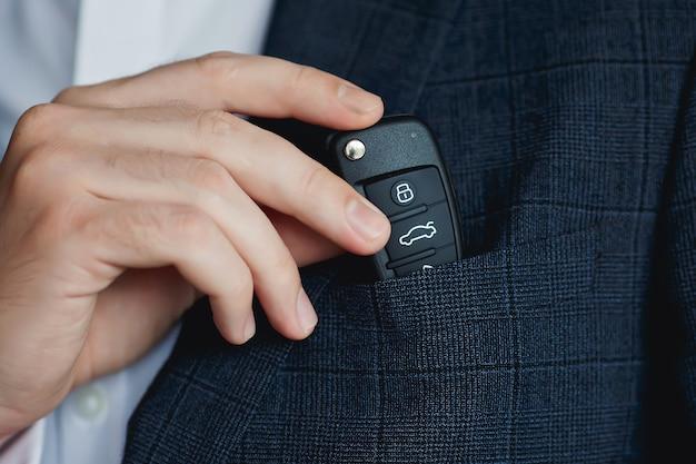 Mężczyzna w garniturze chowa kluczyki do samochodu w kieszeni na piersi.