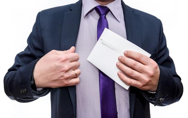Mężczyzna w garniturze chowa kopertę do kieszeni