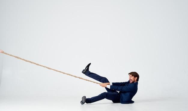 Mężczyzna w garniturze ciągnący pracę zespołową kierownika biura liny