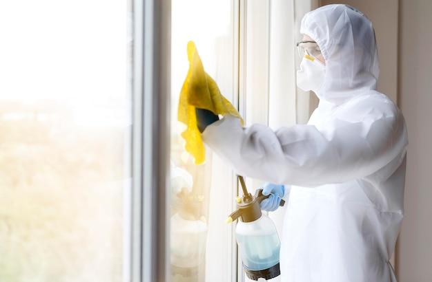 Mężczyzna w garniturze dezynfekujące okno