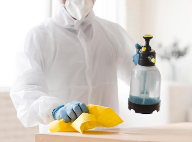 Mężczyzna w garniturze dezynfekujący stół z bliska