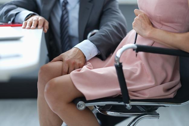 Mężczyzna w garniturze, głaszcząc kolano kobieta sekretarz w pracy zbliżenie. romanse w koncepcji pracy