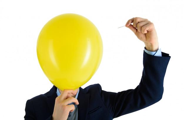 Mężczyzna w garniturze gospodarstwa igły na żółty balon