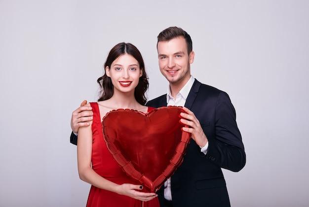 Mężczyzna w garniturze i kobieta w czerwonej sukience trzymają balon w kształcie czerwonego serca na białym tle