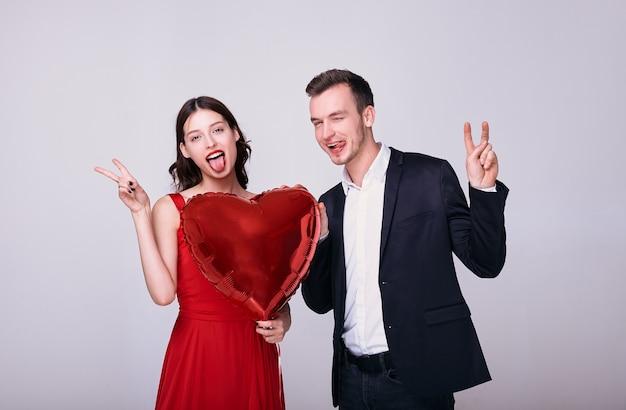 Mężczyzna w garniturze i kobieta w czerwonej sukience trzymają balon w kształcie czerwonego serca robią znak pokoju na białym tle