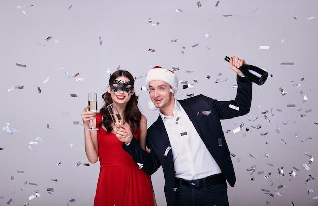 Mężczyzna w garniturze i kobieta w czerwonej sukience z kieliszkami do szampana na szarym tle z konfetti