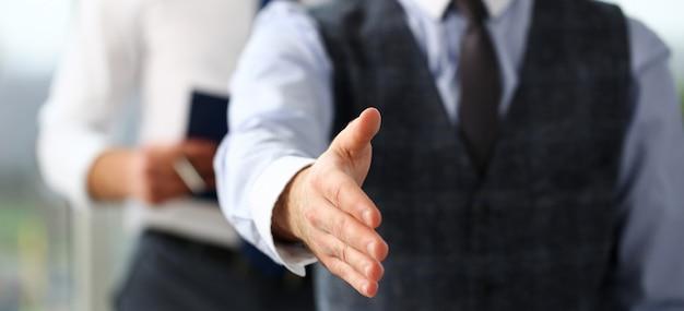 Mężczyzna w garniturze i krawacie podają rękę jak cześć w biurze