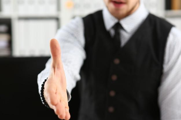 Mężczyzna w garniturze i krawacie podaje rękę jako cześć w zbliżeniu do biura