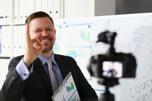 Mężczyzna w garniturze i krawacie pokazuje znak na ramieniu robiąc promocyjny videoblog lub sesję zdjęciową w kamerze biurowej do portretu na statywie. vlogger promocyjne rozwiązanie do selfie lub informacje dotyczące zarządzania doradcą finansowym