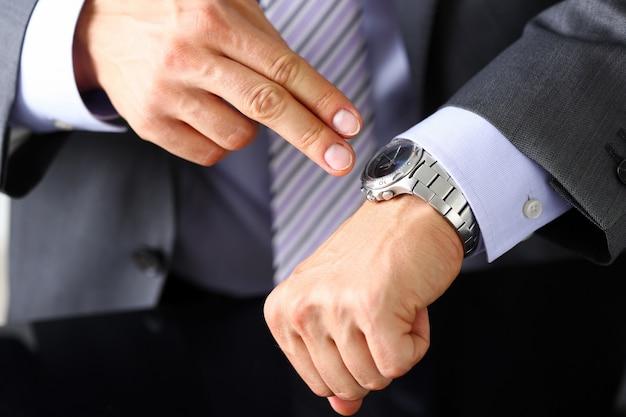 Mężczyzna w garniturze i krawacie sprawdź czas na srebrnym zegarku