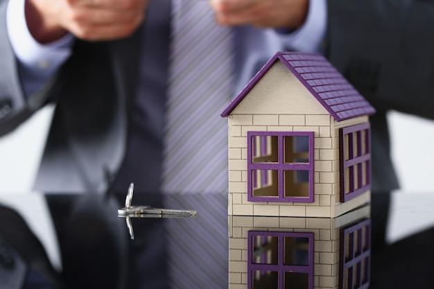 Mężczyzna w garniturze i krawacie, srebrny klucz i niewiele