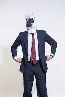 Mężczyzna w garniturze i masce konia na jasnym tle. koncepcyjne tło biznesowe