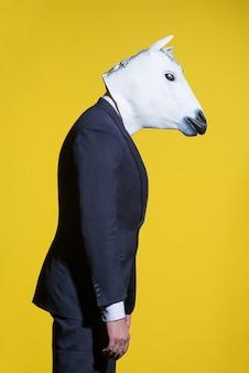 Mężczyzna w garniturze i masce konia na żółtym tle. koncepcyjne tło biznesowe