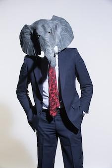 Mężczyzna w garniturze i masce słonia na jasnym tle. koncepcyjne tło biznesowe