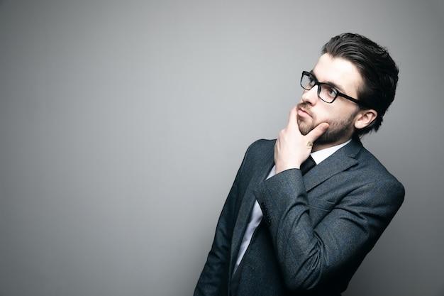 Mężczyzna w garniturze i okularach myśli i dotyka brodą szarej ściany