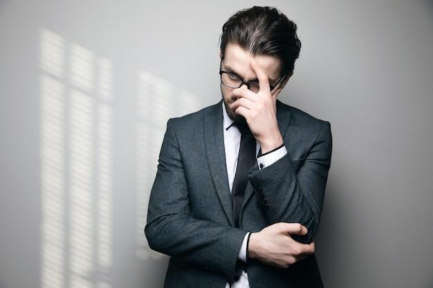 Mężczyzna w garniturze i okularach myśli, trzymając głowę ręką na szarej ścianie