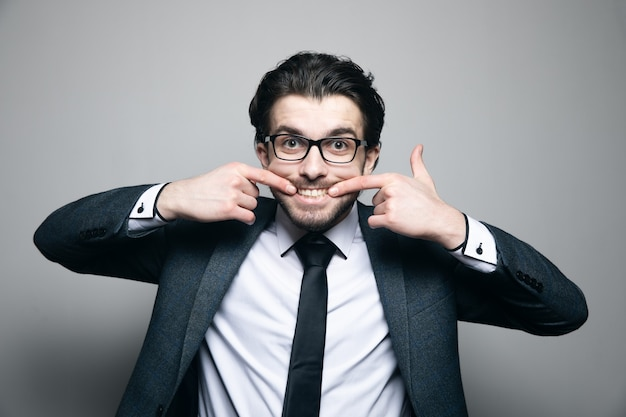 Mężczyzna w garniturze i okularach uśmiecha się palcami na szarej ścianie