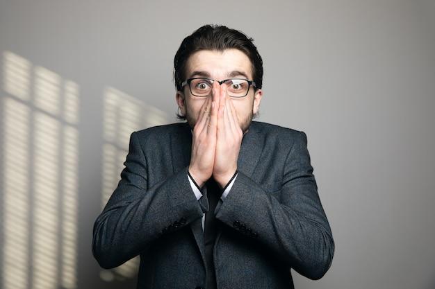 Mężczyzna w garniturze i okularach zamknął usta z zaskoczenia na szarej ścianie