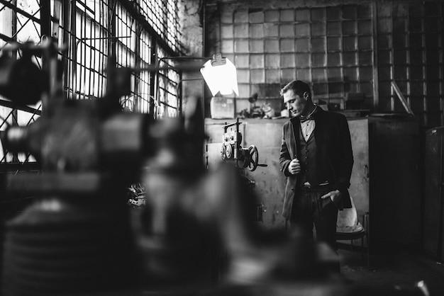 Mężczyzna w garniturze i płaszczu pozuje w eleganckim stroju