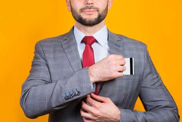 Mężczyzna w garniturze kładzie kartę bankową w zbliżeniu kamana na żółto