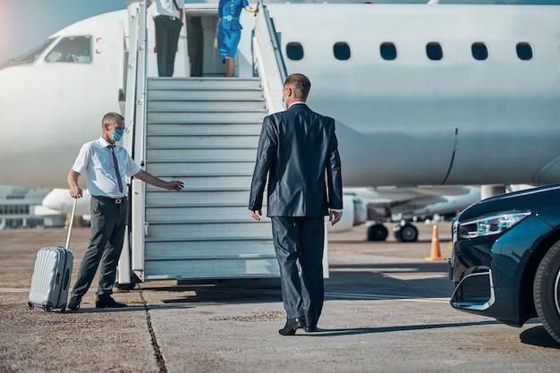 Mężczyzna w garniturze leci na wycieczkę podczas kwarantanny, a asystent wwozi go na pas startowy i niesie bagaż
