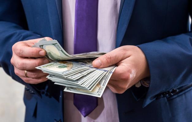 Mężczyzna w garniturze liczący banknoty dolarowe w dłoniach
