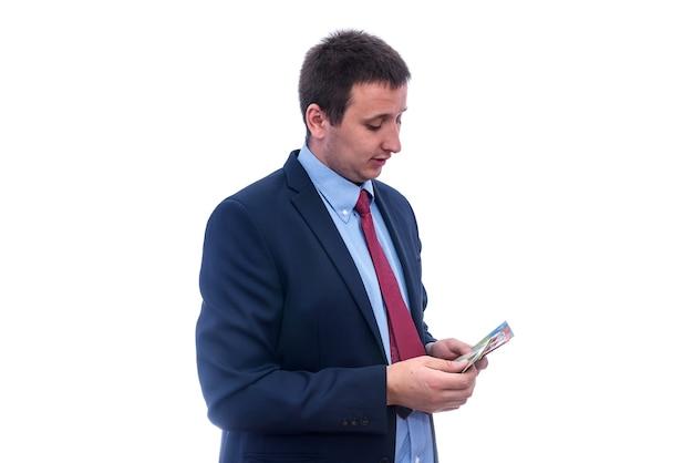 Mężczyzna w garniturze liczący banknoty w dolarach australijskich