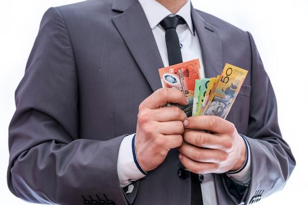 Mężczyzna w garniturze liczący kolorowe dolary australijskie